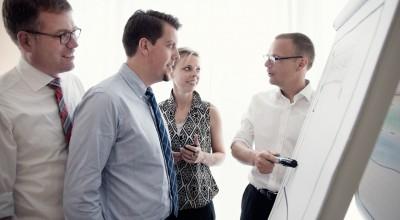 Mitarbeiterführung-Seminar der Führungsakademie Sylt - Teilnehmer betrachten einen Diagramm auf der Tafel und hören die Erklärung des Trainers.